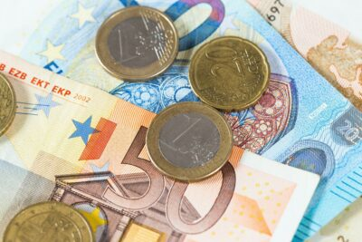 Euro coins lying on banknotes from above in close-up